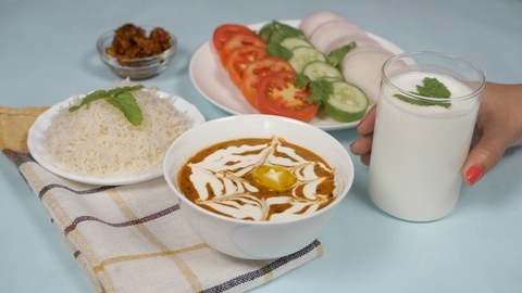 Summer cooler buttermilk drink made of yogurt/dahi placed with dal chawal meal