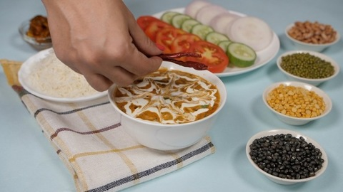 Female's hand putting dried red chilies on top of a fresh bowl of Dal Makhani