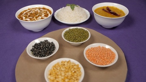 Raw lentils / Dal kept on a rotating table with a cooked meal of Dal-Chawal