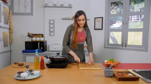 A tall housewife chopping carrots to prepare her dish - Indian Kitchen