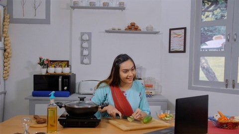 Housewife waving on a video call to her friend while chopping vegetables for salad