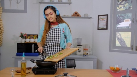 A caring mother cooking vegetables in a frying pan while listening and singing songs