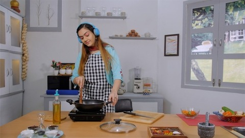 Attractive Indian girl happily cooking or preparing food in her modern kitchen