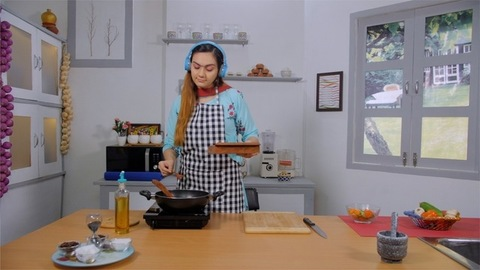 Happy young woman adding spices to the food in the pan while enjoying music