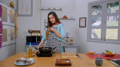 Beautiful young woman cooking food, while looking recipes on her smartphone