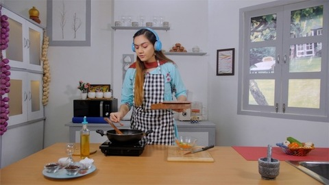 A young housewife adding spices to the food while listening to music