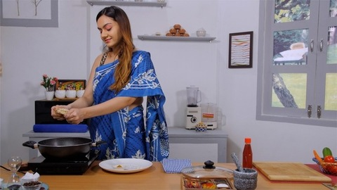 Pretty Indian woman in a saree making noodles in a pan at her modern kitchen