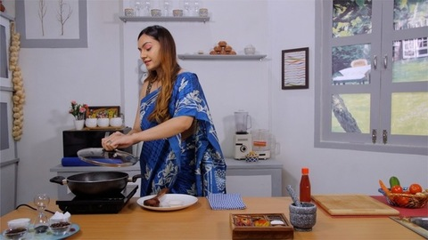 A portrait of a lady in saree cooking inside a kitchen and adding spices to the food