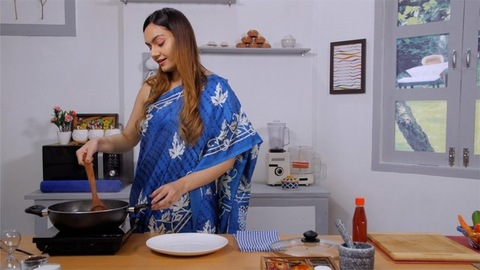 A young and beautiful Indian mother cooking traditional Indian dish in a non stick pan