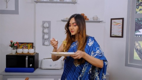 Medium shot of a beautiful Indian female eating hot noodles at her kitchen