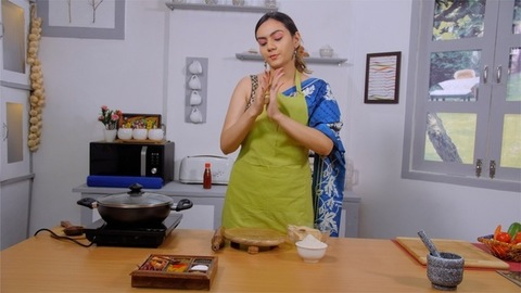 Medium shot of a beautiful housewife preparing chapatis (Indian bread) in a modern kitchen