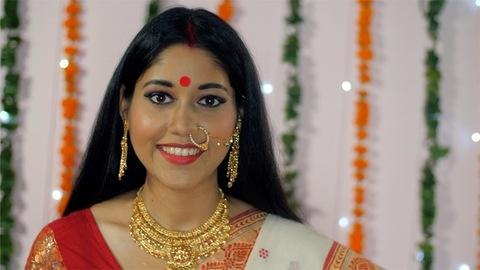 Pretty Bengali woman putting a big red bindi while looking towards the camera