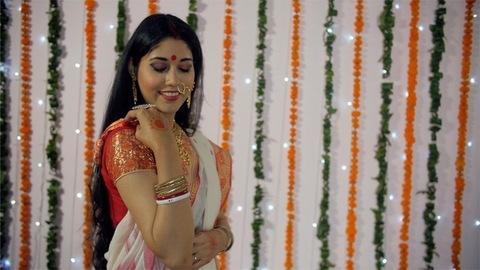 Beautiful Bengali woman draping her sari pallu and smiling towards the camera