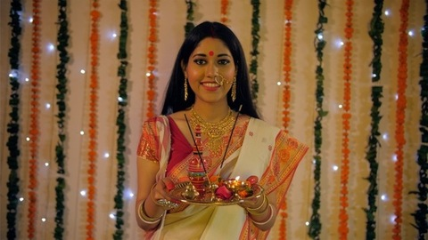 Portrait of a beautiful Indian female smiling while holding a puja thali in her hands