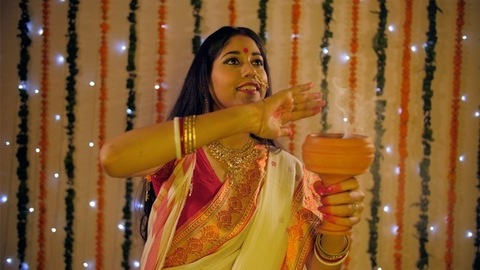 Bengali woman roaming in her house while holding a Dhunuchi (incense burner)