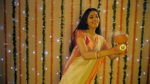 A Bengali housewife doing aarti holding a Bengali incense burner in hands - Dhunuchi dance