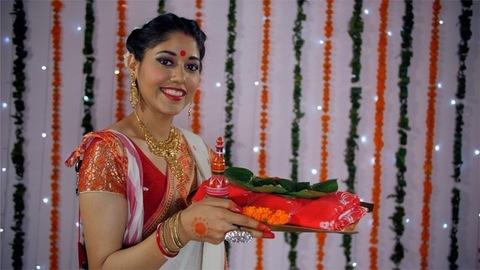Bengali woman in ethnic saree happily holding a plate with religious offerings