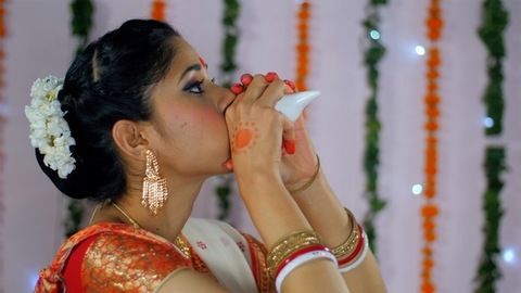 Bengali woman blowing a conch shell during the Durga Puja celebrations in India