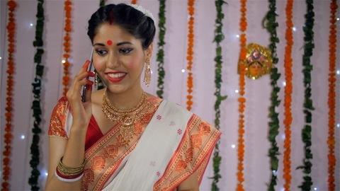 Racking focus shot of a beautiful Bengali woman talking on her mobile phone