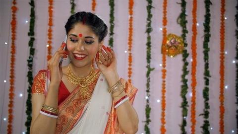 Pretty Bengali woman talking on a phone call while wearing an ethnic sari/saree