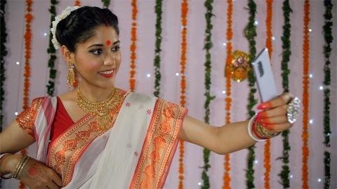 Beautiful Bengali woman happily taking selfies during the Durga Puja celebration