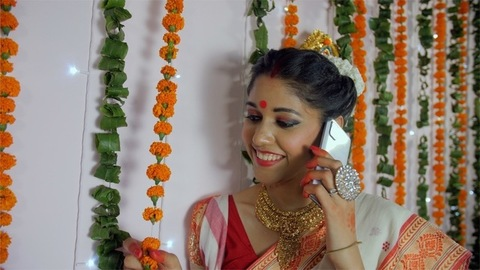 Beautiful Indian female happily greeting her friends over a call on Durgotsava