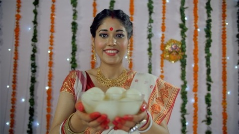 A beautiful Bengali lady offering a bowl full of sweets (Rasgulla) during a festival