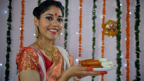 Beautiful Bengali female happily holding a plate of traditional Indian sweets