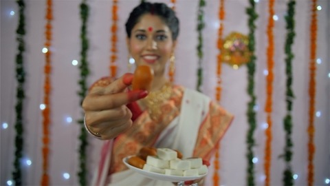A young Bong Beauty offering a famous Bengali sweet during the festival - Durga Puja