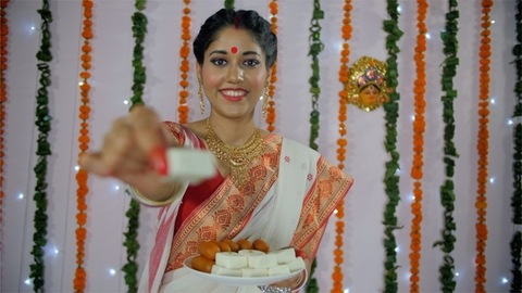 An attractive woman offering delicious Indian sweets with a smile on her face