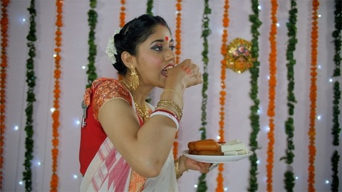 Beautiful Bengali woman eating sweets on Durga Puja festival celebrated in India