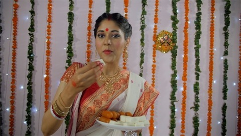 An Indian woman in a traditional Bengali saree eating sweets (Bengali Sandesh)