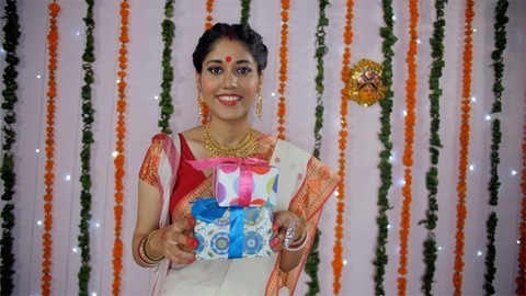 Pretty Indian woman in Bengali saree/sari carrying colorful Durga Puja presents