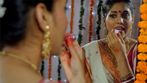 A Bengali woman in a red-bordered saree getting ready for a traditional function