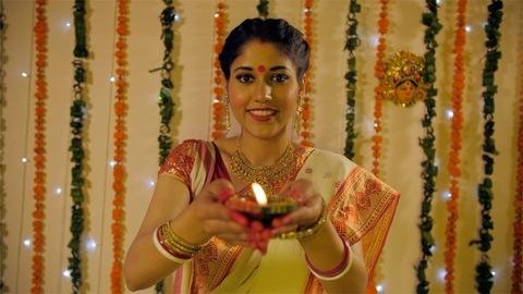 A beautiful wife in a Bengali saree holding a Diya for Durga Puja rituals