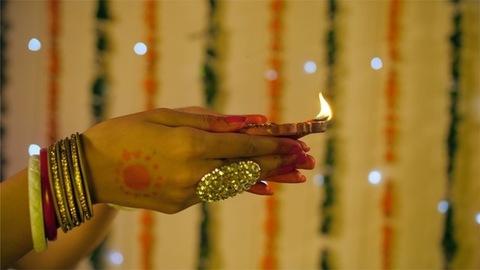 A close-up shot of a beautiful Indian woman's hand holding an oil lamp/Diya