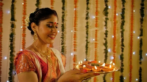 A confident lady dressed in traditional attire holding earthen Diyas - Diwali