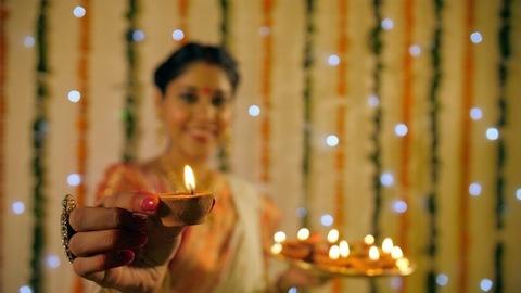 A pretty Bengali wife celebrating Diwali/Deepawali by holding little earthen lamps