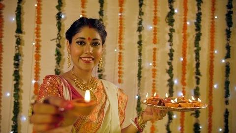 An Indian Bengali wife celebrating Deepawali by lighting traditional earthen lamps