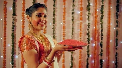 A cheerful housewife holding a plate of Sindur for Sindur Khela in Bengali Festival