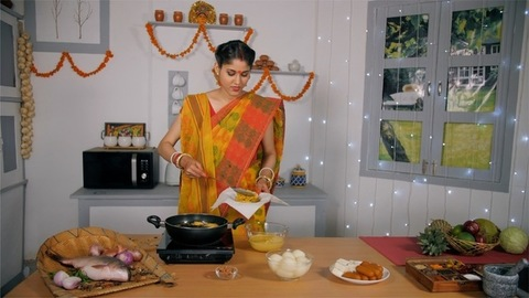 A fair looking Bengali lady cooking a traditional tasty dish (pakoras) in her kitchen