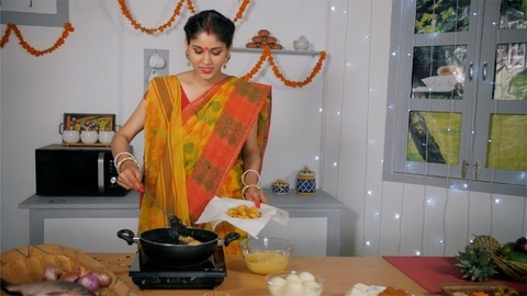 A beautiful Bengali woman frying tasty cutlets (Aloo Chop) for her family members