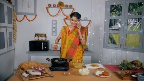 A newly wedded girl busy talking with her mother on mobile while cooking