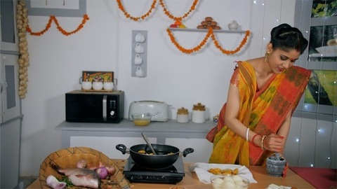 A Bengali wife grinding spices in a traditional grinder - Indian Food