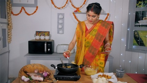 A pretty housewife making tasty snacks while checking the recipe on smartphone