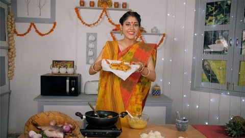 An Indian Bengali wife cooking and presenting her food - festival scene