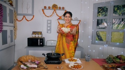 A traditional Bengali woman offering a bowl full of sweets (Rasgulla) to her guests