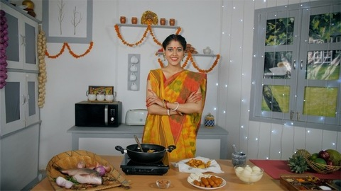 A newly wedded Bengali wife looking confident while cooking food in the kitchen