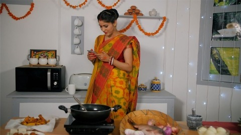 A Bengali beautiful lady chatting on her smartphone in her decorated kitchen