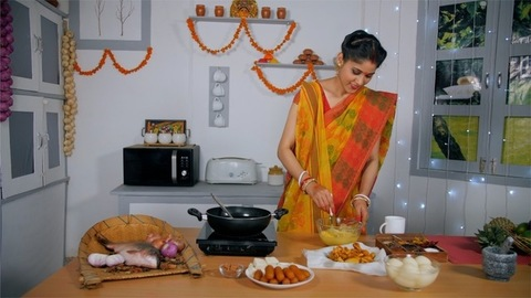 Bengali housewife adding spices to her pakora batter - Food preparation